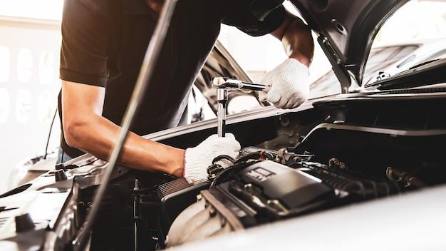 Gros plan de mécanicien automobile à l'aide d'une clé pour réparer un moteur de voiture.