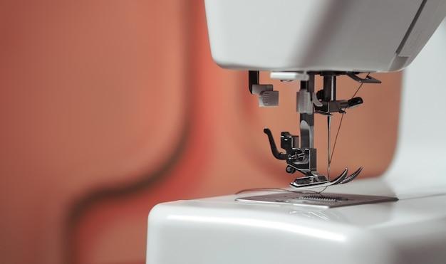 Gros plan sur le mécanisme de l'aiguille de la machine à coudre dans les murs rouges boutique de couture