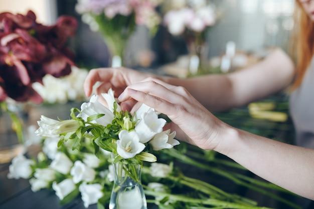 Gros plan, de, méconnaissable, femme, ajustement, fleurs blanches, dans, vase, quoique, faire, bouquet, dans, fleuriste