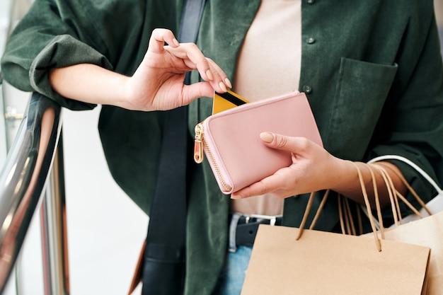 Gros plan, de, méconnaissable, femme, dans, chemise, tenue, sacs papier, et, sortir, carte crédit, hors bourse
