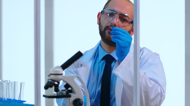 Gros plan d'un médecin chimiste fatigué travaillant dans un laboratoire scientifique équipé moderne. scientifique travaillant avec diverses bactéries, échantillons de tissus et de sang, recherche pharmaceutique pour les antibiotiques