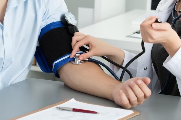 Gros plan médecin mesurant la pression artérielle de son patient