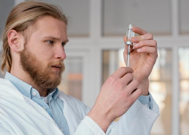 Gros plan médecin préparant l'injection