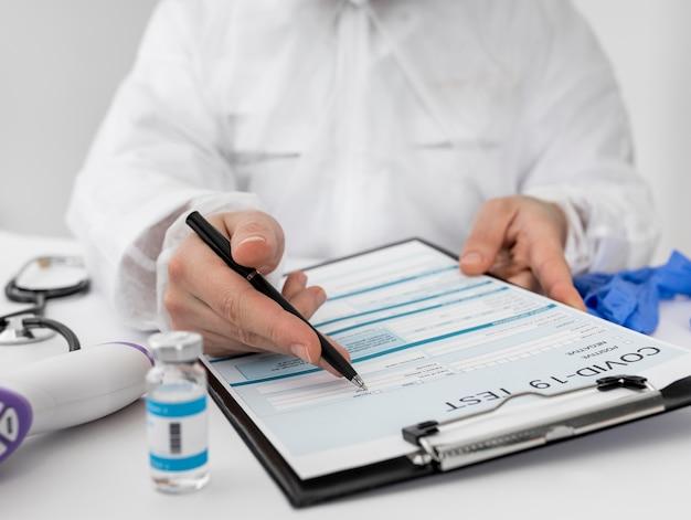 Gros plan médecin remplissant le formulaire médical covid