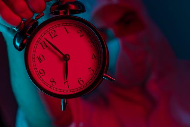 Gros plan: un médecin de sexe masculin portant des vêtements de protection tient un réveil. il est temps de rester à la maison.