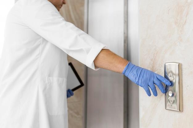 Gros plan d'un médecin touchant les boutons de l'escalator