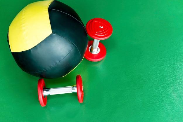 Gros plan de médecine-ball et deux haltères de levage
