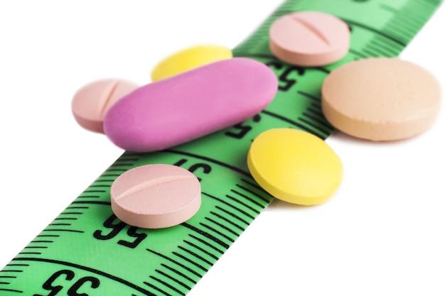 Gros plan sur les médicaments colorés sur le ruban à mesurer vert sur la surface blanche