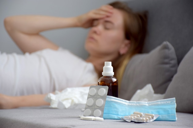 Gros plan sur les médicaments, comprimés, sirop, pilules et masque de protection et jeune femme touchant son front avec la main et souffrant de maux de tête