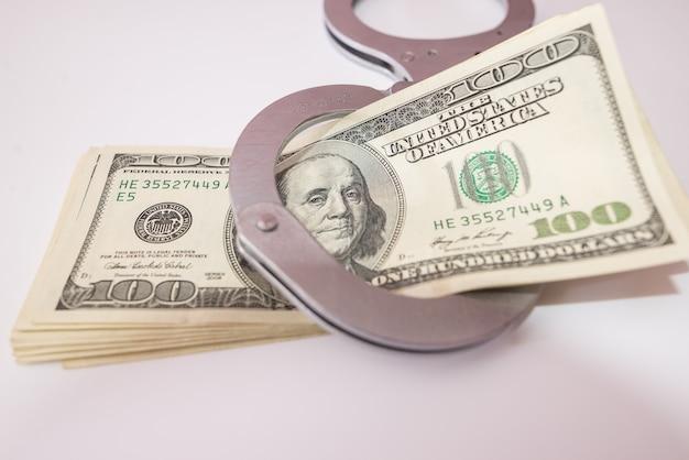 Gros plan sur des menottes en argent et des dollars américains sur le concept de crime blanc.