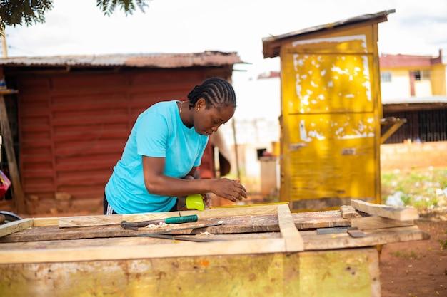 Gros plan d'un menuisier professionnel prenant la mesure du bois sur lequel elle veut travailler