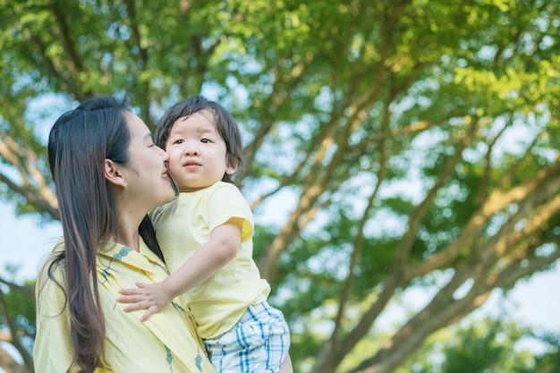 Gros plan mère asiatique tenir fils et embrasser à sa joue en vue de parc texturé fond