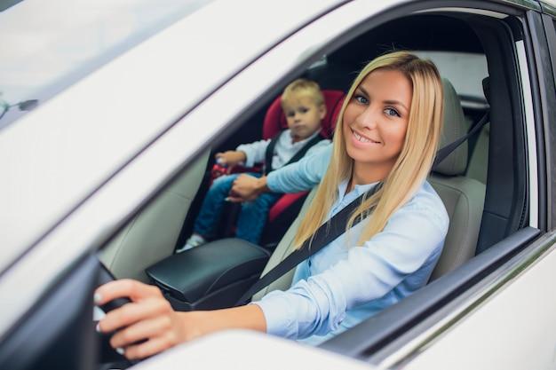 Gros plan, mère, conduire, voiture, boucle, ceinture de sécurité. fils sur le siège arrière. famille, tenue, pouces haut