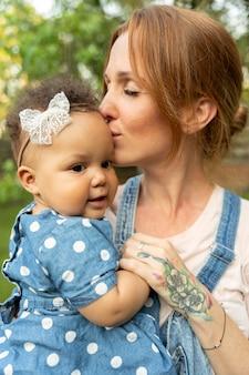 Gros plan mère embrassant bébé sur la tête
