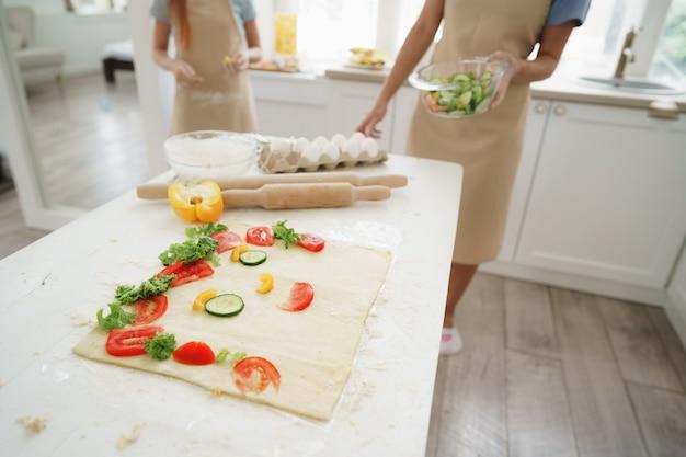 Gros plan sur une mère et sa fille préparant une pizza végétalienne dans la cuisine