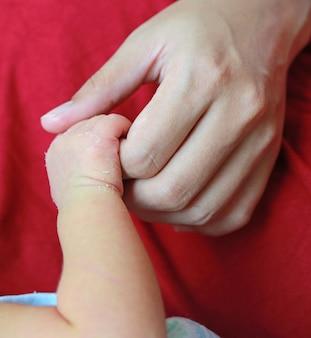 Gros plan de la mère tenant la main de bébé. concept d'amour et de famille.