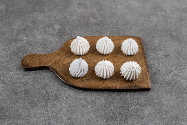 Gros plan de meringue blanche sur planche de bois