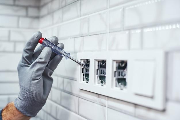 Gros plan sur la mesure du réseau électrique du bricoleur senior définissant de nouvelles prises