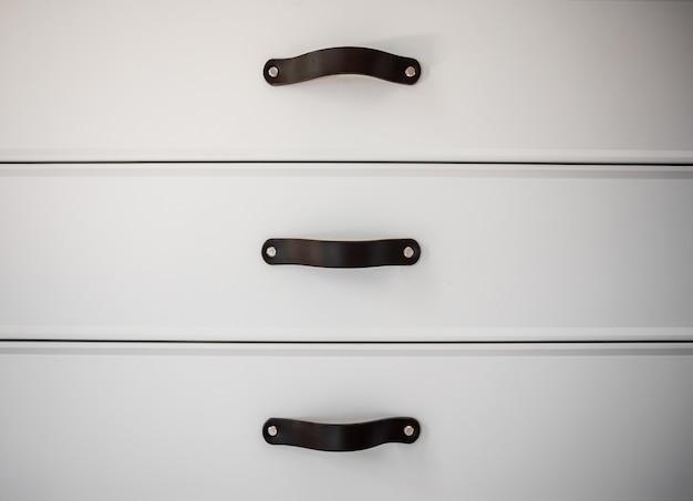 Gros plan sur des meubles blancs minimalistes avec poignées noires, armoires de cuisine, détails.