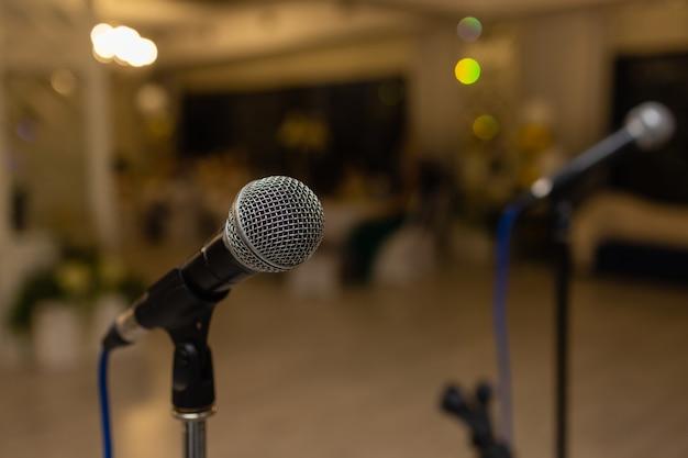 Gros plan d'un microphone sur un résumé flou d'un participant dans une salle de séminaire ou une salle de conférence