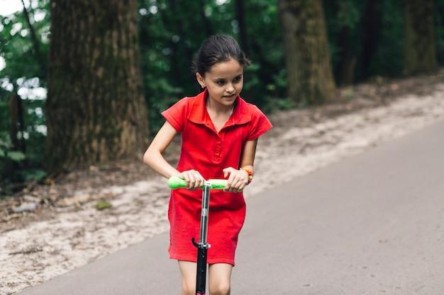 Gros plan, mignon, fille, équitation, pousser, scooter