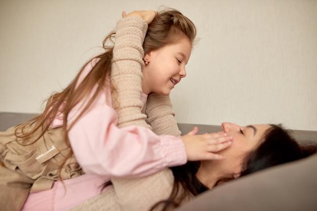 Gros plan de mignonne petite fille d'âge préscolaire jouer avec la jeune mère, petite fille câlin embrasse maman heureuse