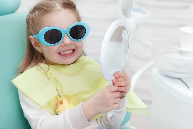 Gros plan d'une mignonne petite fille portant des lunettes de protection assis dans un fauteuil dentaire