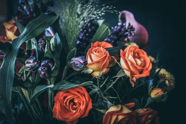 Gros plan sur la mise au point sélective d'un bouquet de fleurs avec des roses orange et des fleurs violettes