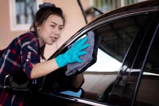 Gros plan et mise au point sélective des femmes asiatiques portant des gants verts nettoyant la fenêtre de la voiture noire avec microfibre