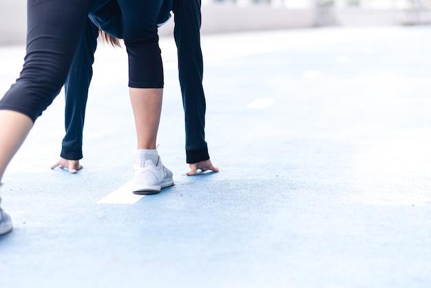 Gros plan de la mise au point sélective pied de femme avec une sneaker sur une piste de course se préparant à commencer.
