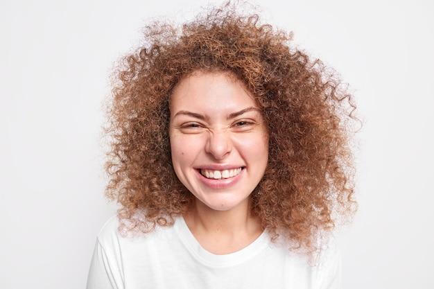 Gros plan d'un modèle féminin européen sincère et heureux qui s'amuse avec des sourires narquois face à la joie a des cheveux bouclés et touffus habillés d'un t-shirt décontracté souriant positivement isolé sur un mur blanc. notion d'émotions