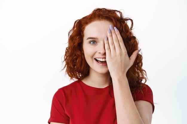 Gros plan d'un modèle féminin rousse joyeux avec une coiffure frisée, fermer la moitié du visage avec la main et sourire excité, mur blanc