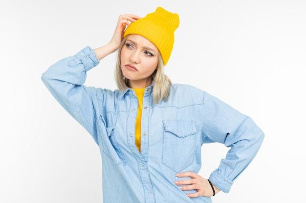 Gros plan d'un modèle de fille pensive dans une élégante chemise en jean avec une coupe de cheveux blonde sur un fond de studio blanc