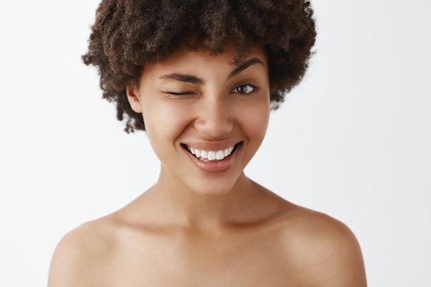 Gros plan d'un modèle à la peau sombre attrayant, joyeux et sympathique avec une coiffure afro posant nu, souriant largement et clignotant comme s'il faisait allusion à un concept intéressant ou secret