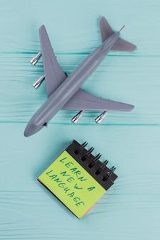 Gros plan d'un modèle réduit d'avion et de papier collant sur fond de bois bleu. vue d'en-haut. apprenez une nouvelle langue sur l'autocollant.