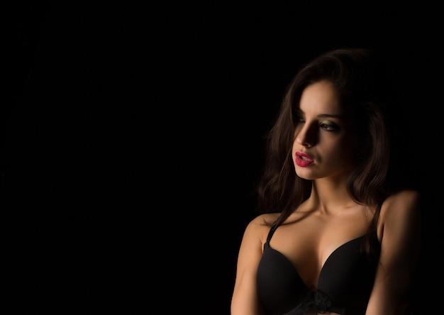 Gros plan d'un modèle sensuel avec un maquillage lumineux posant avec les épaules nues dans l'ombre