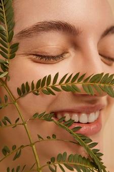 Gros plan modèle smiley posant avec plante