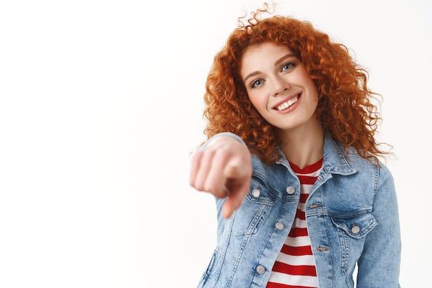 Gros plan moderne élégant gingembre fille cheveux bouclés tête inclinée amusé souriant largement gentil sourire pointant l'index appareil photo faire le choix de vous décider grand candidat, debout mur blanc