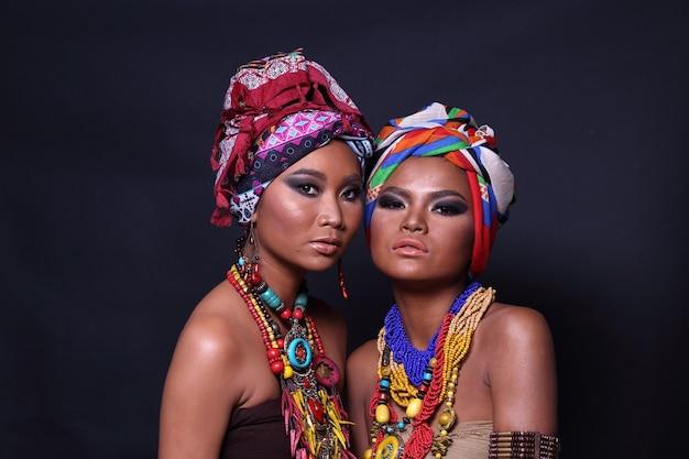 Gros plan sur la moitié du corps des deux femmes asiatiques des années 20 avec la mode constituent le style de la tribu des collines africaines. les filles à la peau bronzée se sentent fortes, souriantes, heureuses avec des accessoires ethniques colorés sur fond noir