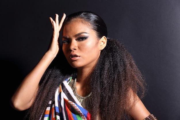 Gros plan sur la moitié du corps d'une femme asiatique des années 20 avec la mode qui composent le style de la tribu des collines africaines. les cheveux d'une fille à la peau bronzée expriment un sentiment fort, sourire avec un accessoire ethnique coloré sur fond noir