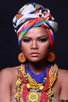 Gros plan sur la moitié du corps d'une femme asiatique des années 20 avec la mode qui composent le style de la tribu des collines africaines. une fille à la peau bronzée exprime un sentiment fort, souriant, heureuse avec un accessoire ethnique coloré sur fond noir