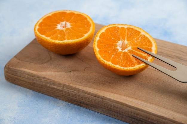 Gros plan de la moitié de la mandarine clémentine coupée sur planche de bois