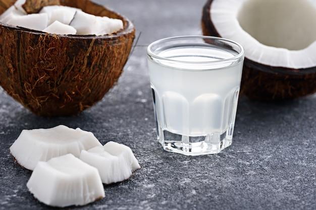 Gros plan des moitiés de noix de coco et de l'eau de coco en verre tourné sur fond gris