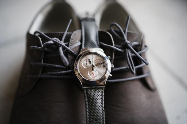 Gros plan d'une montre-bracelet sur des chaussures marron.