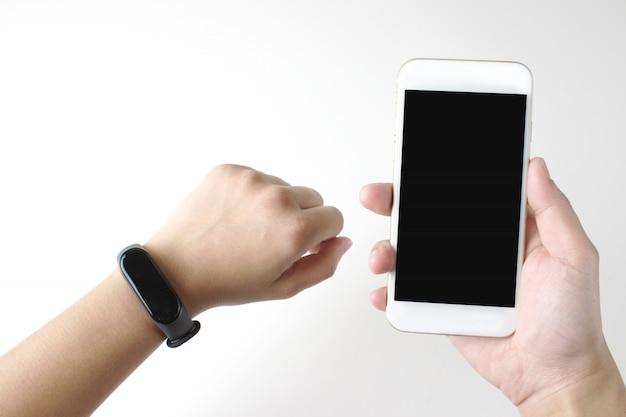 Gros plan d'une montre-bracelet numérique intelligente sur un poignet. les femmes sont prêtes à tenir un téléphone portable.