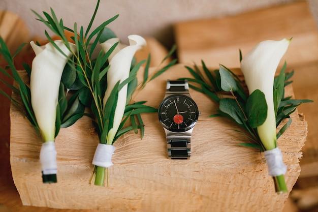 Gros plan d'une montre pour homme noir sur une texture en bois avec des boutonnières avec des lis calla blancs.