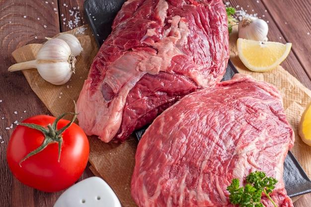 Gros plan de morceaux de boeuf cru juteux sur parchemin. légumes et épices autour. composition des aliments. vue de dessus, mise à plat.