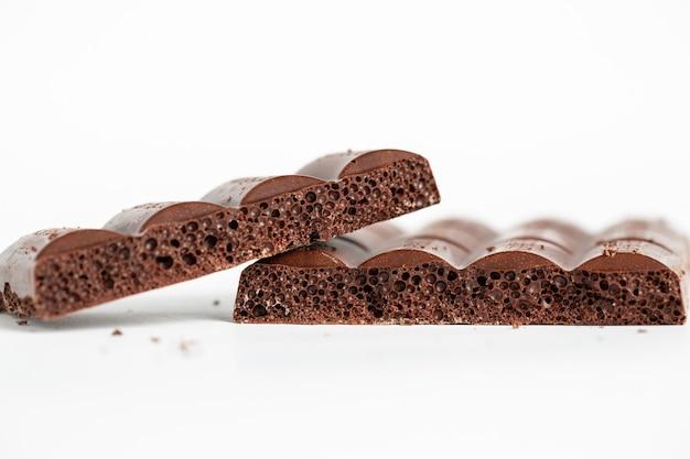 Gros plan sur des morceaux de chocolat à bulles isolés sur fond blanc