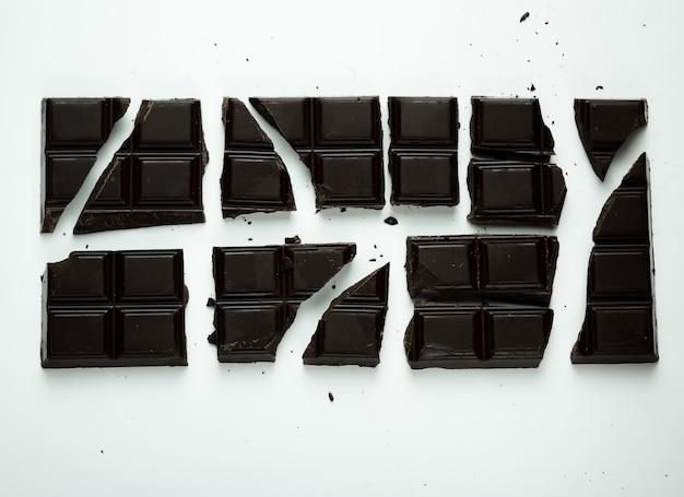 Gros plan sur des morceaux de chocolat noir isolés