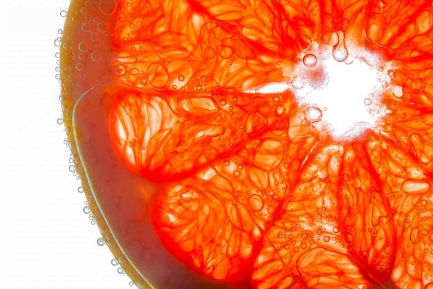 Gros plan de morceaux de pamplemousse avec des bulles sur des fibres juteuses